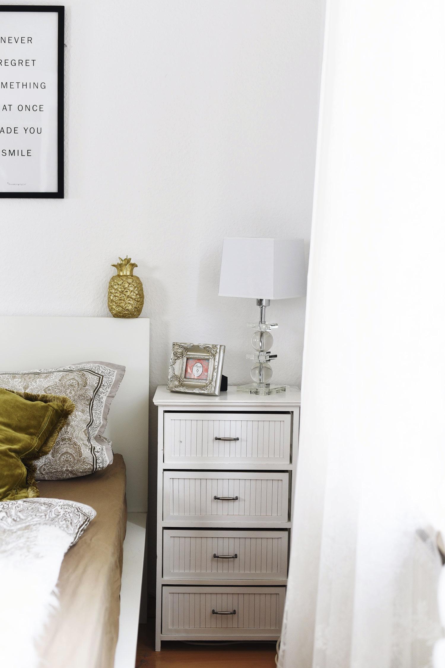 nachttisch-mit-kleiner-stehlampe-glasfuß-bilderrahmen-und-ananas-kerze-nina-fashiioncarpet