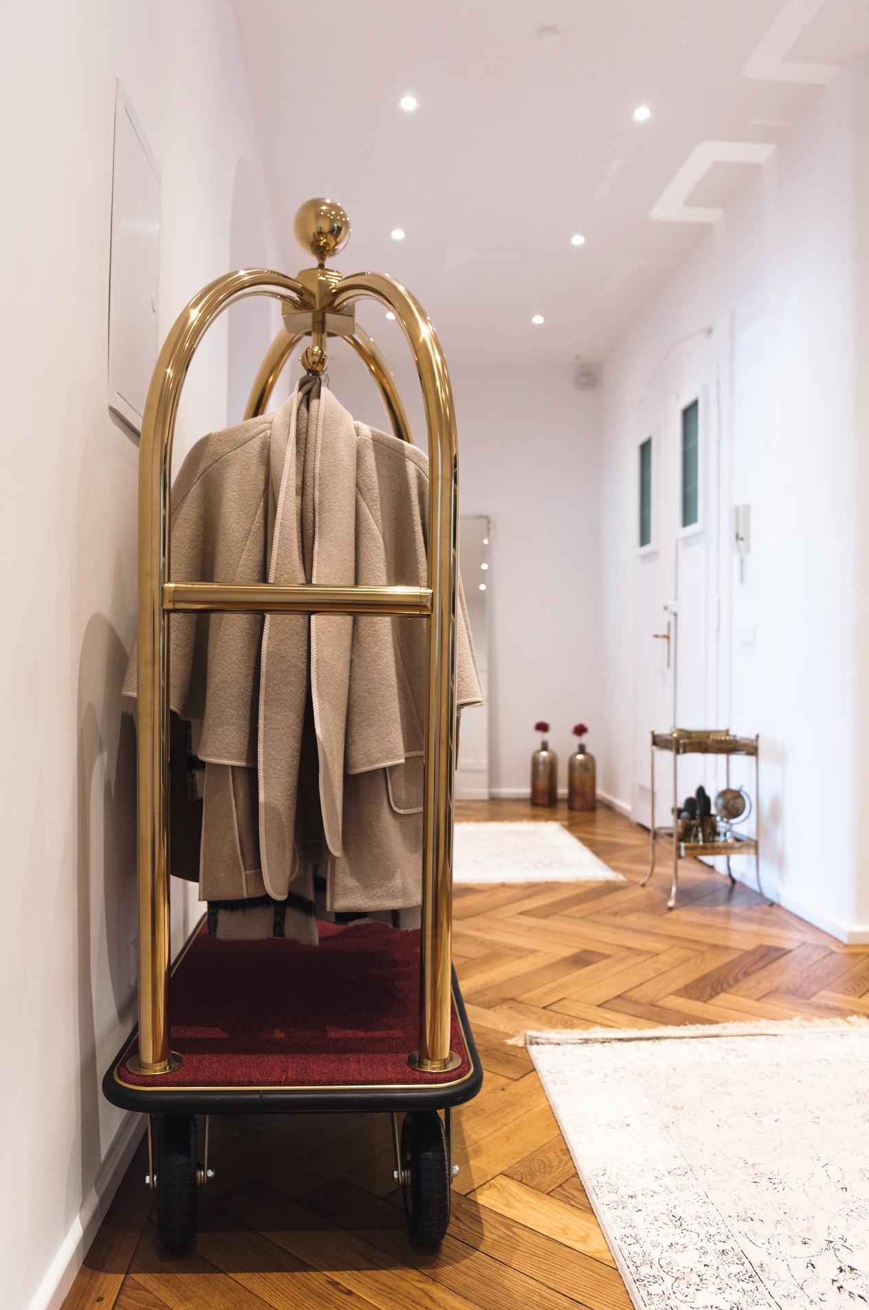 hotel-gepäckwagen-gold-mit-rotem-teppich-als-garderobe-jackenständer-in-der-wohnung-nina-fashiioncarpet-hotelwagen-interior-inspiration-blogger-wohnung