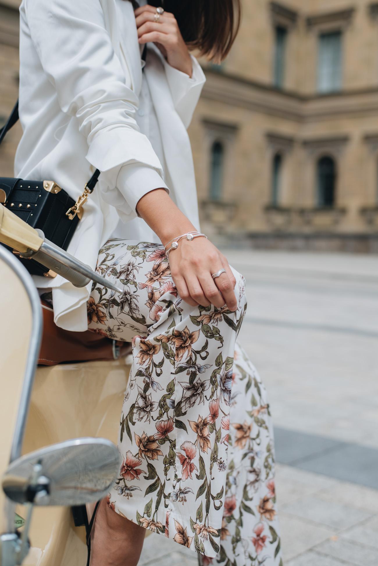 Hose-mit-Blumenprint-H&M-damen-schlaghose-mit-blumen-print-Mango-Koffer-Handtasche-weißer-Sommer-Blazer-nina-schwichtenberg-fashiioncarpet
